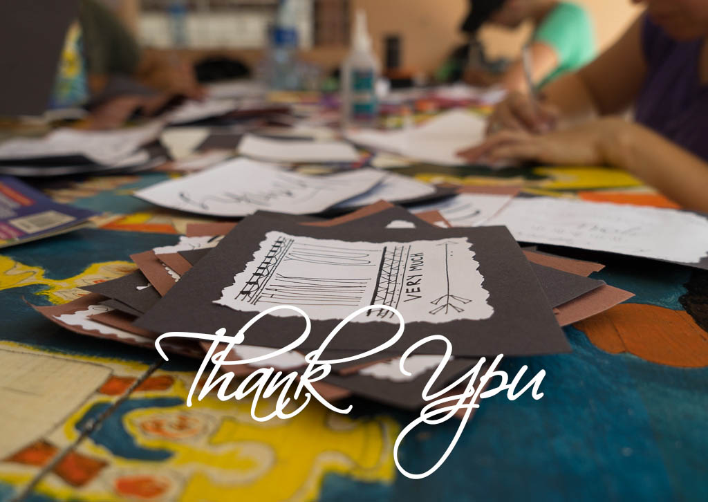 A table is full of letters and art materials and the words Thank You are written across the picture