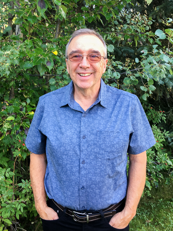 Tim Carter, Light and Salt Ministries Board of Trustees Chairperson, stands in front of some greenery in a blue shirt and black jeans, smiling.